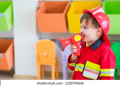 Caucasian boy kid dress up to fireman and use speaker at roll play classroom,Kindergarten preschool education concept
