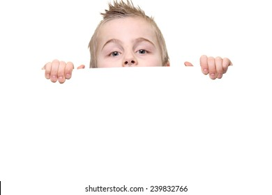 Caucasian boy looking from behind white board