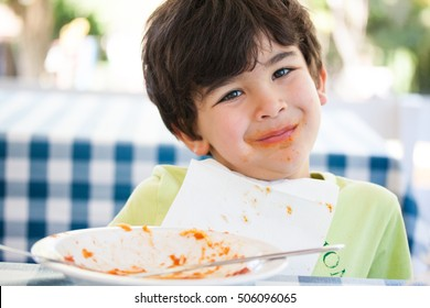 Caucasian boy on table smiling after pasta lunch