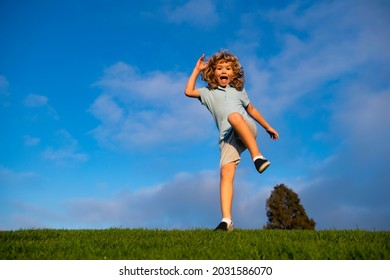 Caucasian boy in a park running and smiling. Happy kid laughing. Emotion face joy child. Joyful, funny spring, summer day, outdoors. Sky background, banner with copy space.