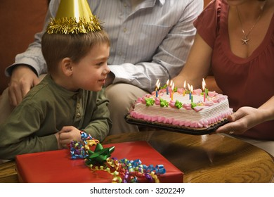 Caucasian boy in party hat with Birthday cake and family.
