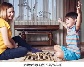 Caucasian boy is playing chess with his mom while sitting on a floor carpet at home. He is celebrating a victory.