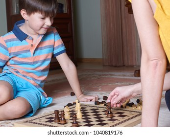Caucasian boy is playing chess with his mom at home.