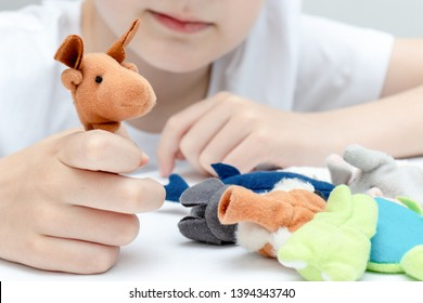 A caucasian boy playing different roles by using finger puppets, toys for expressing his emotions, agression, fear and freandship as a part of psychotherapy.