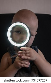 Caucasian boy playing with magnifying glass with backlight.