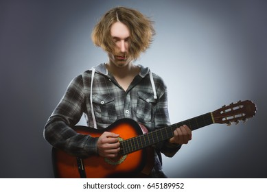 Caucasian boy playing on acoustic guitar. Teenager with classic wooden guitar