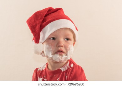 The Caucasian boy put on a Santa Claus hat and smeared his cheeks with shaving foam. He cries with tears.