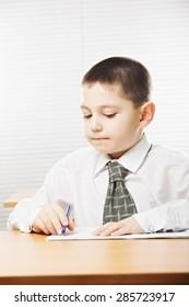 Caucasian boy wearing formal school wear writing at the desk in classroom
