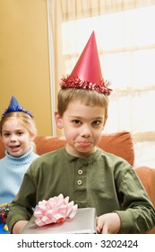 Caucasian boy wearing party hat pouting and looking at viewer.