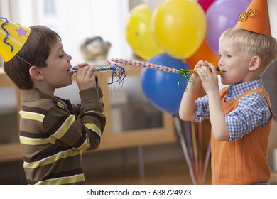 Caucasian boys blowing noise makers at party