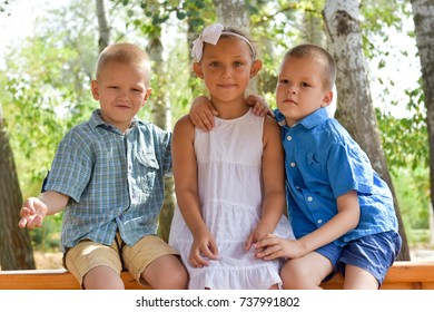 Caucasian boys hug the young girl. The concept of the novel at the resort.