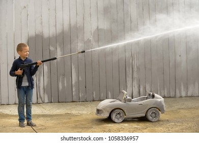Caucasian boys from the orphanage play with a high-pressure sink and try to wash a toy car.