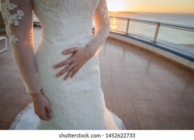 Caucasian bride feeling butterflies in her stomach before getting married at beach sunset