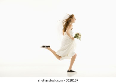 Caucasian bride running and holding bouquet.