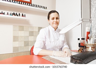 Caucasian brunette manicurist sitting at the red desk in a parlor. Polish bottles in row on the wall racks. Horizontal shot