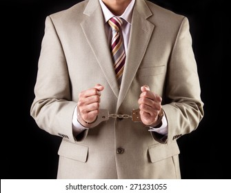 Caucasian business executive wearing a light brown suit and maroon tie in handcuffs. Corrupt businessman is arrested and handcuffed for corporate scam and fraud.