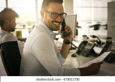 Caucasian business man having conversation on Landline phone. Business man in office. Looking at camera.
