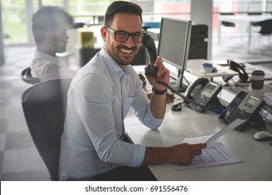 Caucasian business man having conversation on Landline phone. Business man in office. Looking at camera.