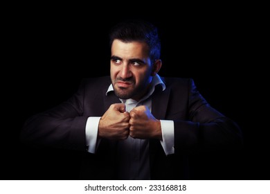 Caucasian business man in suit being angry, thinking to revenge against black background