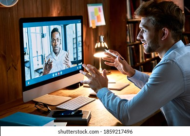 Caucasian business man talking with african male partner coach on video conference call discussing social distance work at virtual remote meeting videoconference chat using pc computer at home office. - Shutterstock ID 1859217496