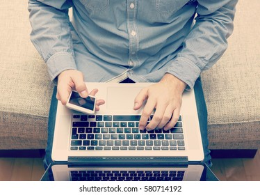Caucasian business man is typing with a mobile phone and a laptop in his lap. Business concept image. Image has a vintage effect applied.