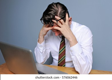 Caucasian business man under pressure in job is emotionally stressed out in front of his computer in the office