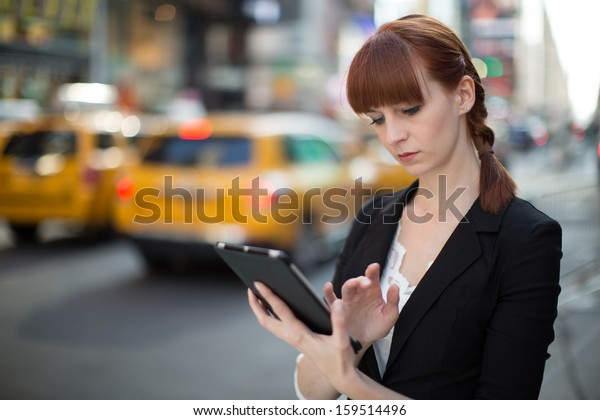 Caucasian business woman in New York City using ipad tablet pc computer reading ebook