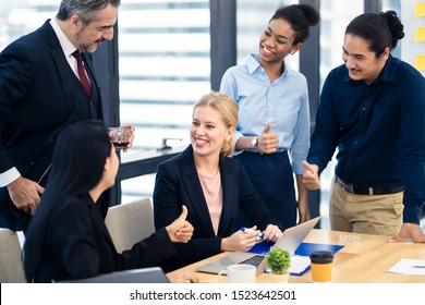 Caucasian business working woman sitting in meeting room receiving complements and congratulations from colleague with various nationalities by giving her thumb ups. The girl feeling happy with smile.