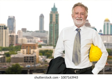 Caucasian Businessman Architect or Engineer, Holding Hard Hat or Helmet, Standing beside Modern City Building on Construction site as Real Estate Land Project Development Executive or Manager Business