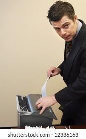 Caucasian businessman furtively shredding documents at his desk