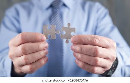 Caucasian businessman holding puzzle pieces.