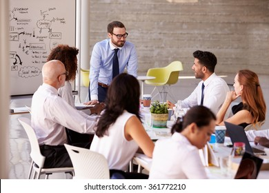 Caucasian Businessman Leading Meeting At Boardroom Table