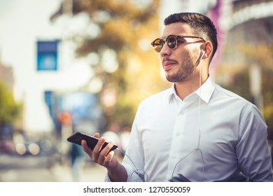 Caucasian businessman is looking good standing on the street, he is looking front with mobile in his hands