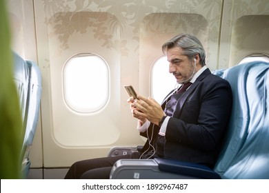 Caucasian businessman mobile checking work or news on airplane cabin. man watching movie or entertainment media waiting for inflight service. working or travel abroad concept
