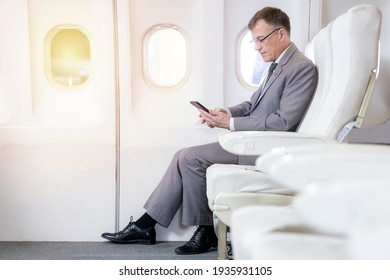 Caucasian businessman passenger airplane sitting comfortable seat working with smart phone area using wireless connection on board, Caucasian businessman mobile checking work, news on airplane cabin.