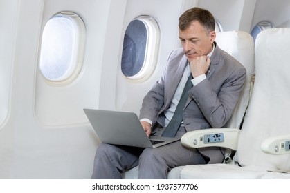 Caucasian businessman passenger on airplane working with computer labtop area using wireless connection on board, Caucasian businessman checking work on airplane cabin.