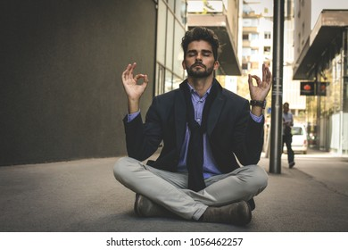 Caucasian businessman practicing yoga in the city. Space for copy.