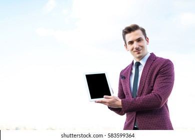 caucasian businessman in red business suit, white shirt, black tie, black trousers and costly watch stand on the roof with empty tablet in hands near his head, look at camera, smiling, show tablet