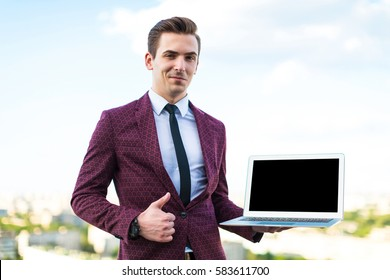 caucasian businessman in red business suit, white shirt, black tie, black trousers and costly watch stand on the roof with laptop in hands, look at camera, show thumbs up blurred city on background