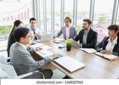 caucasian businessman showing success business profit graph from white board in multiethnic business people meeting with smile and happy face