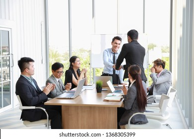 caucasian businessman showing success business profit graph from white board in meeting then they shaking their hands meaning of their job is success with smiling and happy faces.