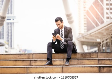 Caucasian businessman sitting down on stairway using and holding his smartphone playing or surfing the internet, wearing suit and tie with tall skylines and architectural structure in the background