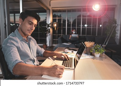 Caucasian businessman sitting happily on desk in living room under warm lamp with flare cicle and twilight blue sky outside house. Idea for working late and lifestyle of freelance, working at home.