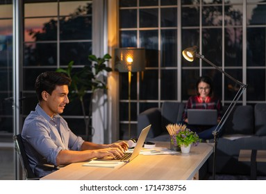 Caucasian businessman sitting happily on desk in living room under warm lamp and twilight blue sky outside house in background. Idea for working late and lifestyle of freelance, working at home couple