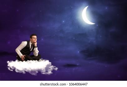 Caucasian businessman sitting on a cloud, wondering