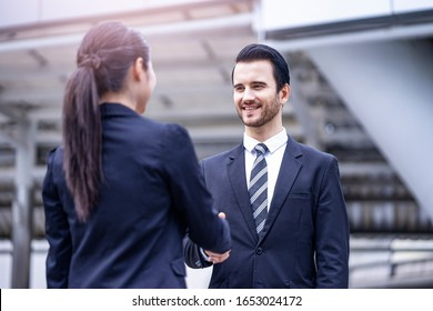 caucasian businessman smiling and standing casually shaking hands with a beautiful asian businesswoman in greetings, outdoor within the city district with urban architectural structure in background