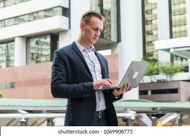 caucasian businessman stand and typing word into laptop, concept of work hard and offsite services