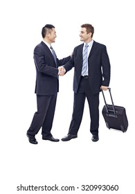 caucasian businessman with suitcase greeted by asian partner, isolated on white background.