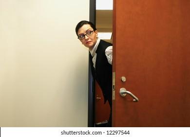 Caucasian businesswoman furtively peeking through a doorway