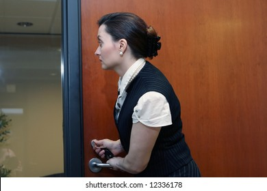 Caucasian businesswoman looking through a glass screen while working the lock on an office door